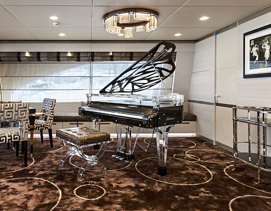 This classic black and transparent version of a baby grand crystal Hive Elegance acrylic piano on a private yacht. Notice how it's semitransparent silhouette lightens its presence in a smaller space. Perfect choice when square footage is a consideration.