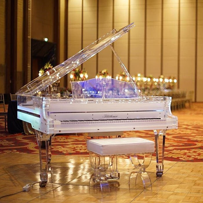 Lucid Elegance baby grand piano looks stunning in this golden tone luxurious lobby. LED illumination ads a touch of futurism and magic to this cinderella-like grand piano.